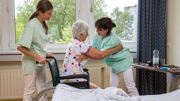 Pflegerinnen helfen einer alten Frau aus dem Bett