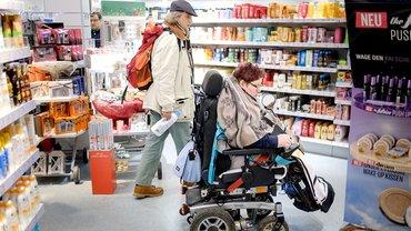 Persönlicher Assistent und Rollstuhlfahrern beim Einkaufen
