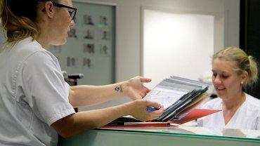 Pflegekräfte im Krankenhaus mit Patientenakten und Computern