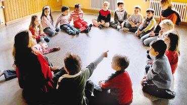 Kinder sitzen im Kreis auf Boden