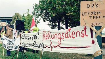 """Rettungsdienst-Beschäftigte mit Banner mit Aufschrift """"Schluss mit Rettungsdienst-Ausschreibung."""" und """"DRK-Reformtarifvertrag jetzt"""""""