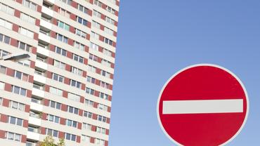 """Seitenansicht eines Hochhauses mit einem """"Sackgassen-Verkehrsschild"""" im Vordergrund"""