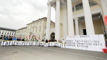 Menschen mit Schildern, die Tarifvertrag bei der Diakonie fordern