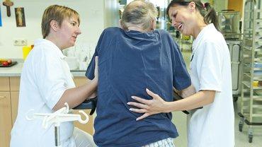 zwei Pflegekräfte mit altem Mann