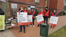 Protest-Teilnehmer*innen mit Plakaten (weniger Zusatztätigkeiten, besserer Personalschlüssel, nie allein in der Gruppe!)