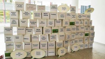 Viele Kartons als Mauer bzw. Wand gestapelt, mit diversen Tätigkeitsbeschreibungen eines Kita-Beschäftigten