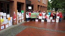 Kita-Beschäftigte stehen mit einer Papp-Karton-Mauer mit aufgeschriebenen diversen Tätigkeitsbeschreibungen von Kita-Beschäftigten vor dem Rathaus in Weyhe
