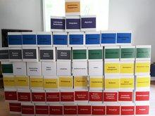 Papp-Kartons als Mauer aufgestapelt mit aufgeschriebenen diversen Tätigkeitsbeschreibungen von Kita-Beschäftigten