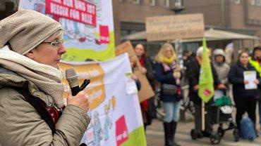 Frau mit Mikro, Menschen mit Bannern im Hintergrund