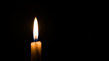 heruntergebrannte Kerze vor dunklem Hintergrund