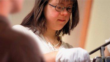Abbildung zeigt eine behinderte Frau mit einem mechnischen Werkzeug