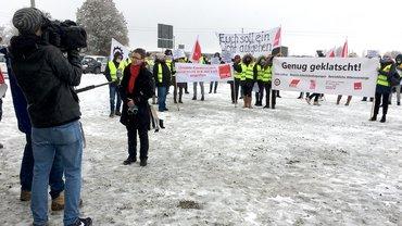 Beschäftigte stehen mit Transparenten auf einem verschneiten Platz. Ein Fernsehteam interviewt die ver.di-Vertreteterin.