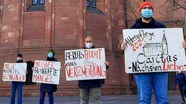 MEnschen mit Plakaten vor Kirche